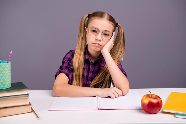 Ragazza intelligente della scuola che fa i compiti alla scrivania