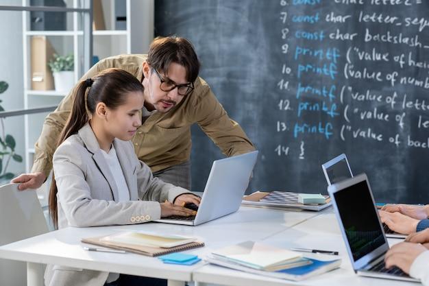Studente intelligente seduto alla scrivania davanti al computer mentre insegnante in occhiali guardando il display e controllando i dati