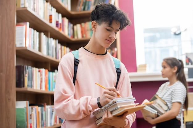 Studente di college adolescente intelligente con la matita che prende appunti in taccuino mentre fa una pausa grande scaffale per libri in biblioteca