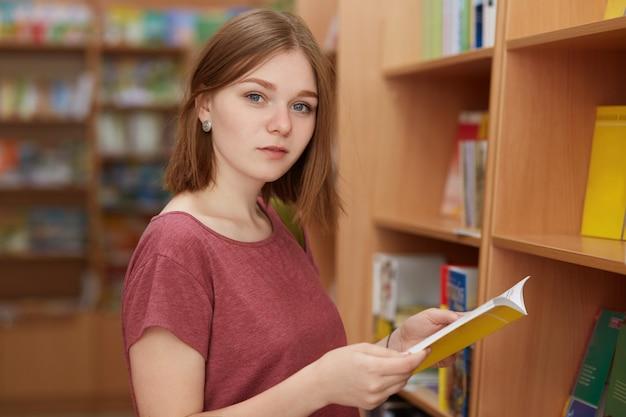 Intelligente giovane femmina con acconciatura bobbed, tiene il libro in mano, pone in biblioteca o in libreria, vestita in maglietta casual, sceglie qualcosa da leggere durante il tempo libero. concetto di hobby e gioventù