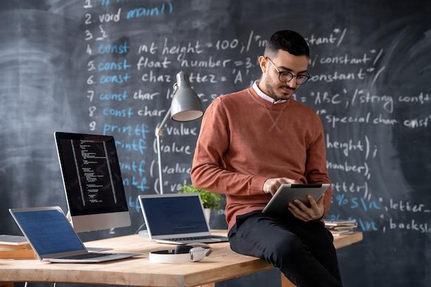 Giovane manager intelligente che utilizza il touchpad mentre è seduto sul tavolo con due laptop e il monitor del computer con dati codificati