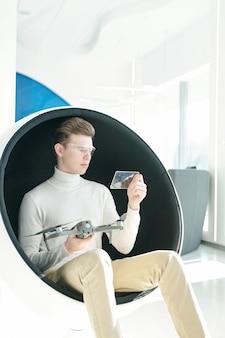 Giovane programmatore intelligente con occhiali intelligenti e abbigliamento casual elegante seduto in poltrona semisferica mentre studia le caratteristiche del drone