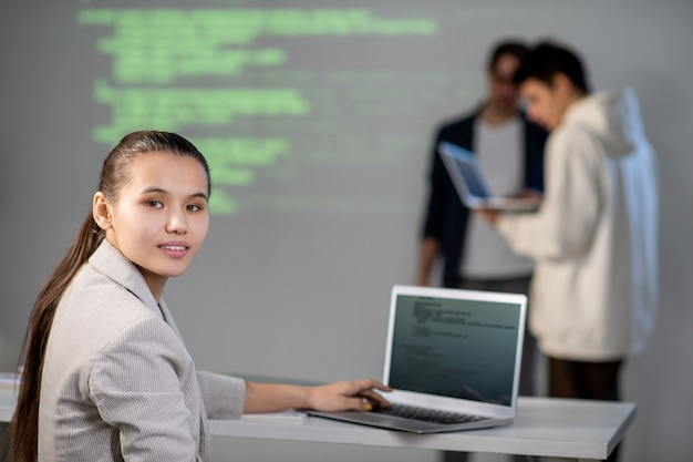Giovane studente intelligente che ti guarda seduto alla scrivania davanti al laptop e prepara la presentazione per una conferenza o un seminario