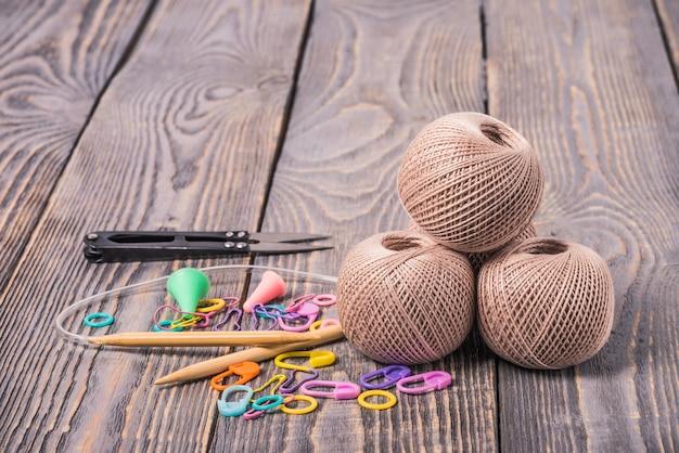 Clews di filato, ferri da maglia, forbici e clip su fondo di legno.