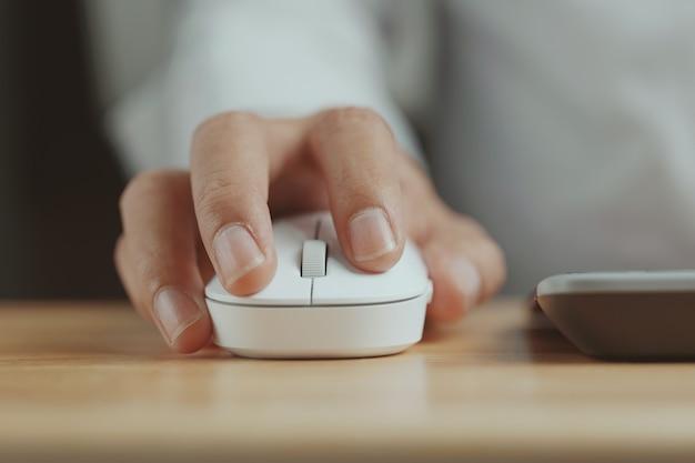 Fare clic con il mouse bianco del computer su una scrivania lavorare con un pc o un laptop