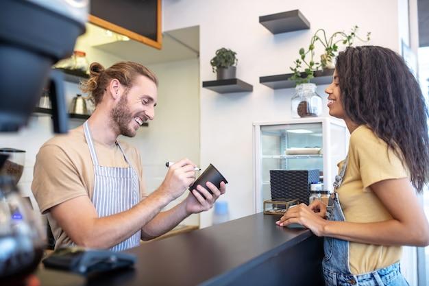 Cliente, bar. ridendo giovane uomo barbuto adulto con pennarello e vetro e donna dai capelli lunghi vicino al bancone che fa ordine nella caffetteria