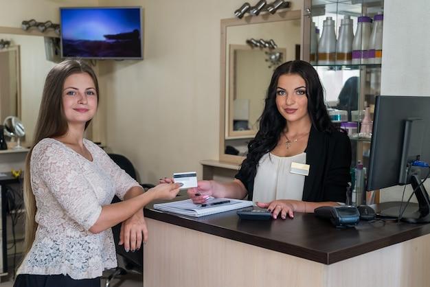 Il cliente dà la sua carta di credito all'amministratore nel salone di bellezza