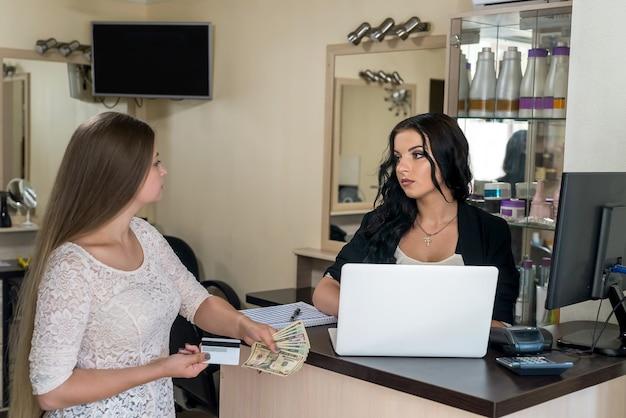 Cliente che dà dollari all'amministratore nel salone di bellezza