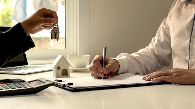 Il cliente sta firmando un contratto immobiliare con un modulo di richiesta mutuo approvato, idee di mutuo ipotecario per la casa e assicurazione sulla casa.