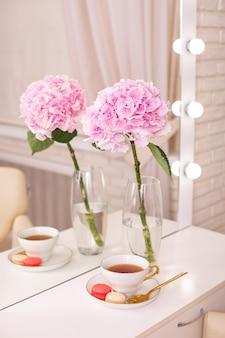 Posto del cliente nel salone di bellezza per parrucchieri con una tazza di amaretti e fiori di tè