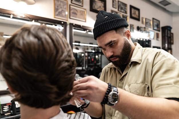 Il cliente riceve un taglio di capelli in un barbiere. cura dei capelli da uomo. taglio di capelli con le forbici