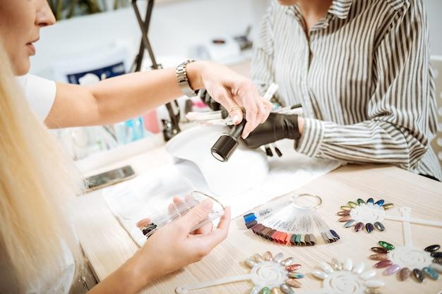 Cliente del salone. clientela bionda del salone di bellezza che sceglie il colore della gommalacca prima di fare la manicure