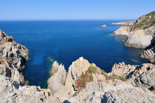 Scogliere a picco sul mare sotto il cielo blu - penisola revellata, corsica - francia