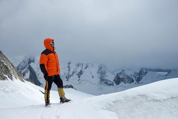 Alpinista scalatore si trova sulla cima della montagna. cime innevate e cielo, altai, belukha