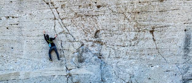 Uno scalatore scala una montagna su un bunner di pietra