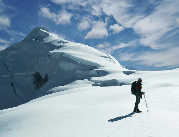 Scalatore in una montagna innevata