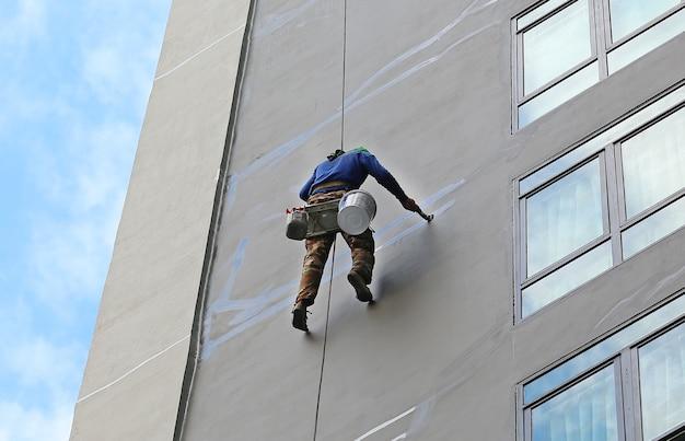 Lavoratore dello scalatore che appende sulle corde per riparare servizio di costruzione su grattacielo.