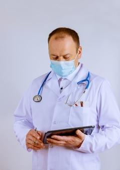 Medico ospedaliero di emergenza clinica medico del lavoro utilizzando la tavoletta digitale mentre si trovava vicino alla scrivania