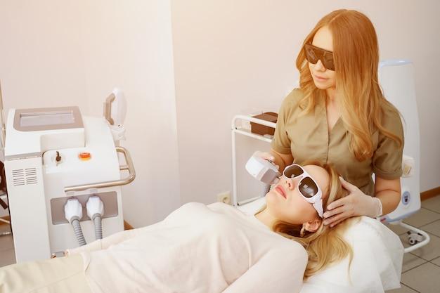 L'operatore della clinica esegue la depilazione radicale sul viso della ragazza