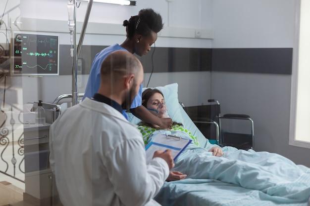 Team clinico che monitora la donna malata che mette la maschera di ossigeno monitorando la salute respiratoria