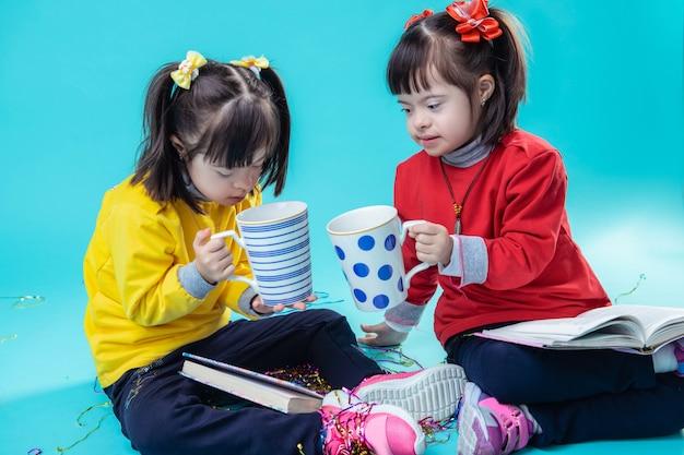 Tazze giganti tintinnanti. bambine dai capelli corti che ispezionano l'interno di grandi tazze mentre riposano sul pavimento e si divertono insieme