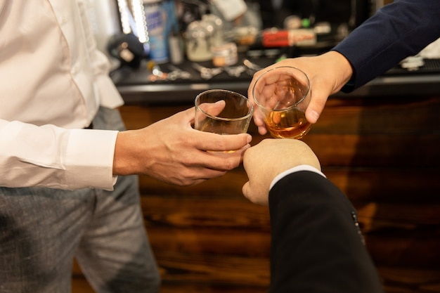 Bicchieri tintinnanti con bevande alcoliche e un pugno, bicchiere tintinnio