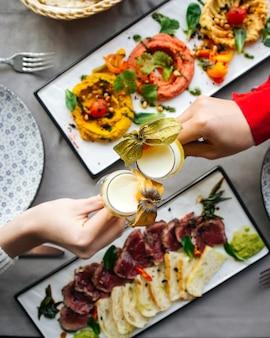 Tintinnanti bicchierini di cocktail aspri e schiumosi sopra il tavolo del ristorante servito