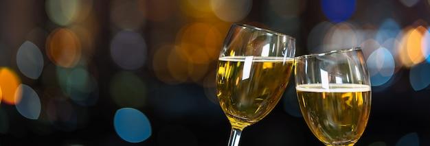 Tintinnio con due boccali di birra o bicchieri sopra la foto sfocata di paesaggio urbano per festeggiare