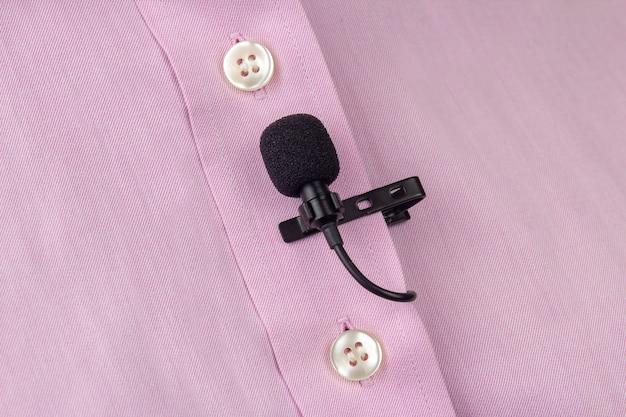 Un microfono lavalier a clip è attaccato a una maglietta rosa, primo piano. registrazione audio del suono della voce su un microfono a condensatore.