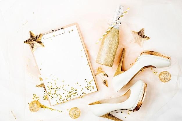 Appunti e scarpe da donna con decorazioni dorate. concetto di vacanza alla moda piatto, vista dall'alto.