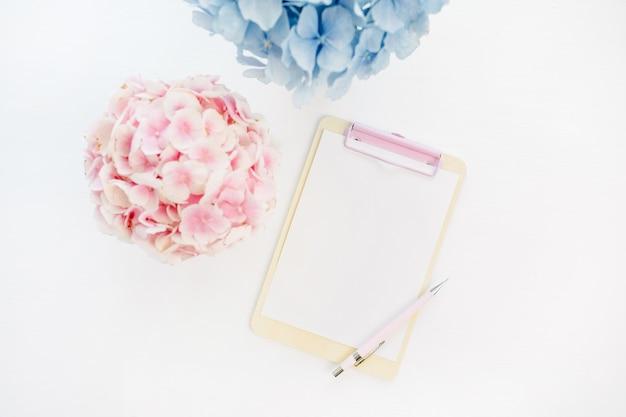 Appunti mock up e mazzi di fiori di ortensie pastello pallido su superficie bianca