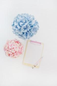 Mockup di appunti e mazzi di fiori di ortensie pastello pallido su superficie bianca