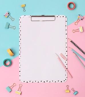 Appunti, penna, legante, matita e nastro adesivo al tavolo creativo rosa e blu.