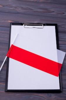 Appunti con carta bianca e bandiera bicolore della polonia