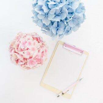 Appunti con spazio di copia e mazzi di fiori di ortensie pastello pallido su superficie bianca