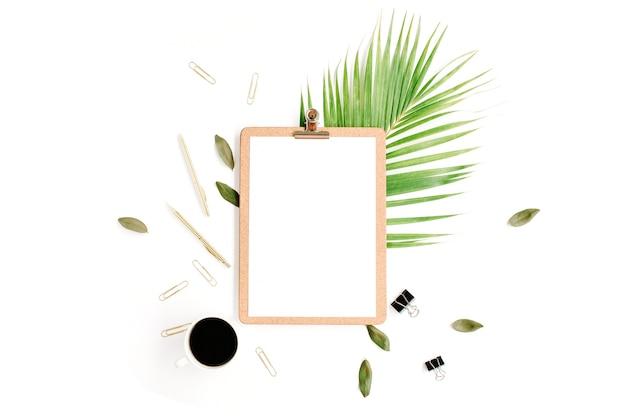 Appunti con copia spazio vuoto vuoto, tazza di caffè, penna dorata e clip, petali e ramo di palma su sfondo bianco.