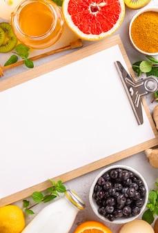 Appunti con prodotti sani per aumentare l'immunità o la vista dall'alto di alimenti dietetici. frutta e verdura per rafforzare il sistema immunitario