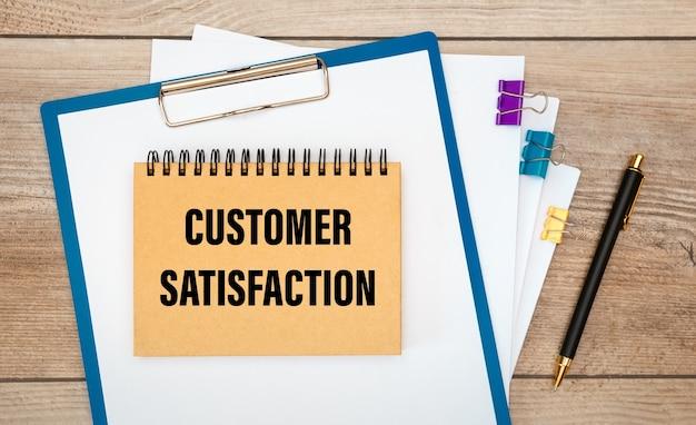Appunti con la scritta documenti sulla soddisfazione del cliente e una penna su un tavolo di legno
