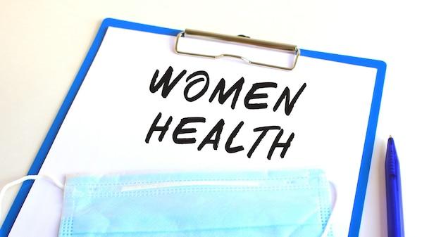 Una lavagna per appunti con maschera protettiva medica si trova su un tavolo. iscrizione donne salute.