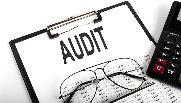 Appunti con testo audit con calcolatrice, penna e grafico. concetto di affari.