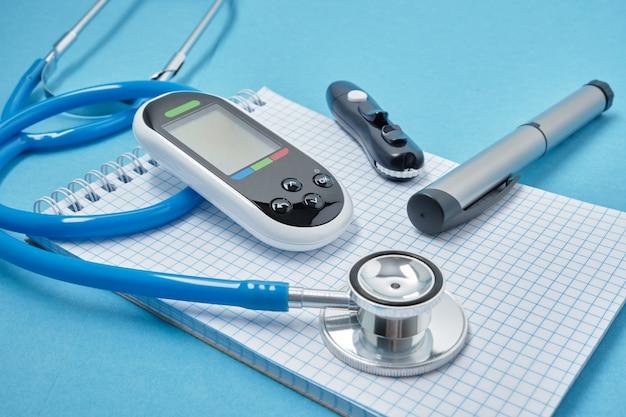 Appunti con fogli di carta bianchi bianchi, stetoscopio, glucometro, lancetta e penna a siringa con insulina su sfondo blu, concetto di giorno daibet, diagnostica del diabete