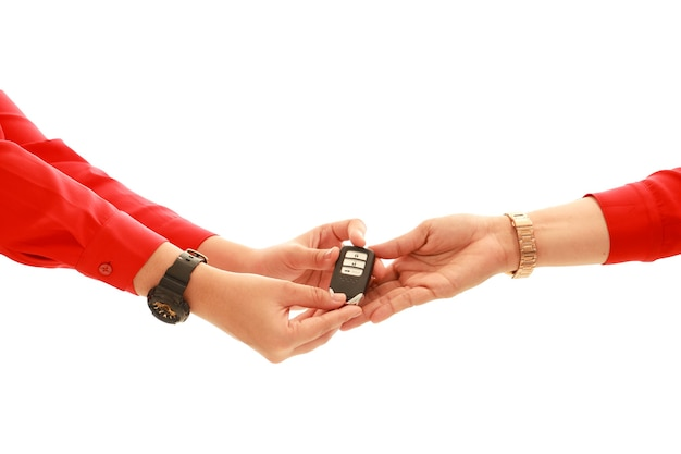 Le donne del percorso di ritaglio passano con la camicia rossa che dà la chiave moderna dell'automobile alla mano delle donne su fondo bianco concetto di trasporti. vendere o acquistare concetto.