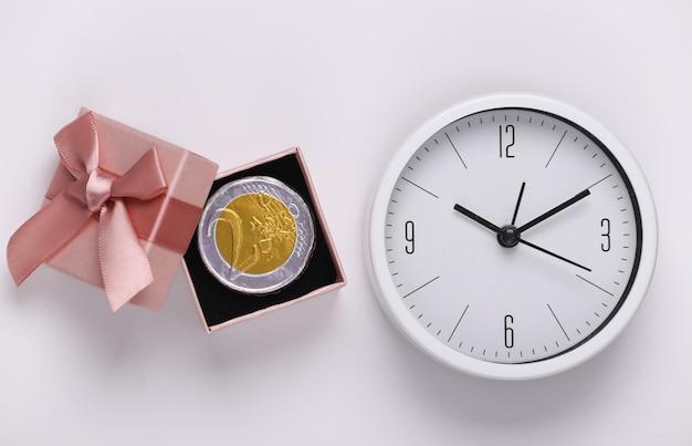 Orologio e confezione regalo con moneta su sfondo bianco