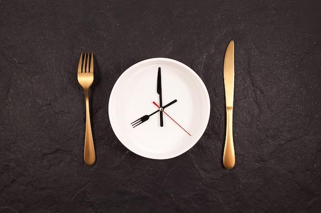 Lancette dell'orologio su un piatto bianco. forchetta e coltello d'oro su un tavolo di pietra scura