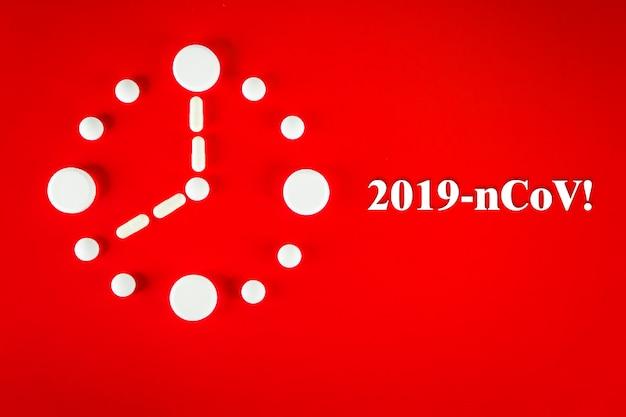 Orologio fatto di compresse bianche con iscrizione 2019- ncov , su sfondo rosso, vista dall'alto. 2019 nuovo concetto di coronavirus 2019-ncov.