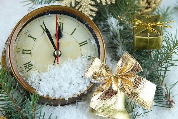 Orologio con rami di abete e decorazioni natalizie sotto la neve da vicino