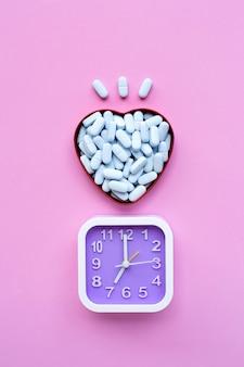 Orologio con pillole blu mediche in scatola a forma di cuore sulla superficie rosa. vista dall'alto