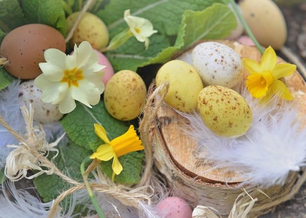 Chiudere le uova di pasqua decorative nascoste nei fiori primaverili nel giardino