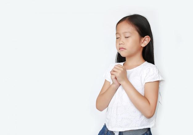 La fine osserva la bella piccola preghiera asiatica della ragazza del bambino isolata con lo spazio della copia. spiritualità e concetto di religione.