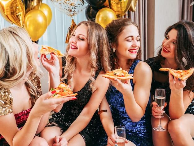 Chiudere gli amici femminili seduti in camera decorata con palloncini, divertendosi. signora che condivide la sua fetta di pizza con la migliore amica.